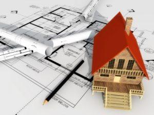 wooden model house on building plans blueprint